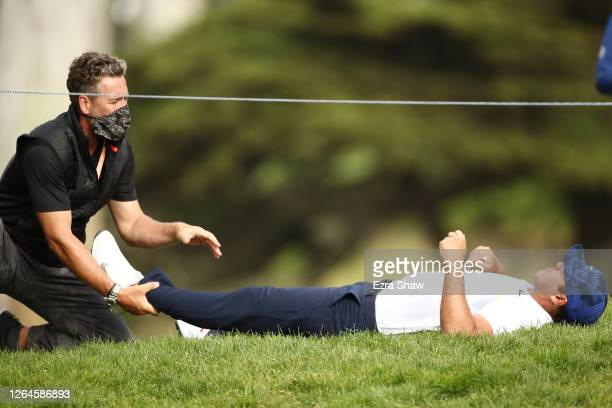 Brooks Koepka of the United States is stretched out on the 12th hole by physical therapist Marc Wahl during the second round of the 2020 PGA...