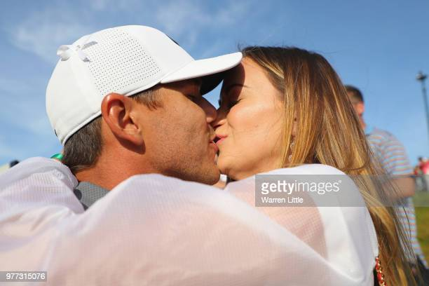 Brooks Koepka of the United States kisses girlfriend Jena Sims as they walk off the 18th green during the final round of the 2018 US Open at...