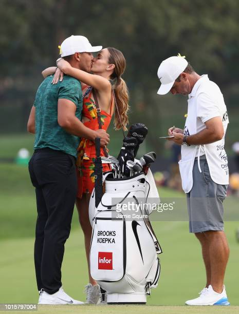 Brooks Koepka of the United States kisses his girlfriend Jena Sims after winning the 2018 PGA Championship with a score of 16 at Bellerive Country...