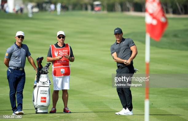 Brooks Koepka of the United States plays a shot on the second hole as caddie Ricky Elliott and coach Claude Harmon III look on during the ProAm ahead...