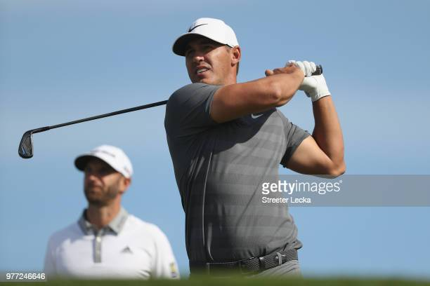 Brooks Koepka of the United States plays his shot from the 12th tee as Dustin Johnson of the United States looks on during the final round of the...