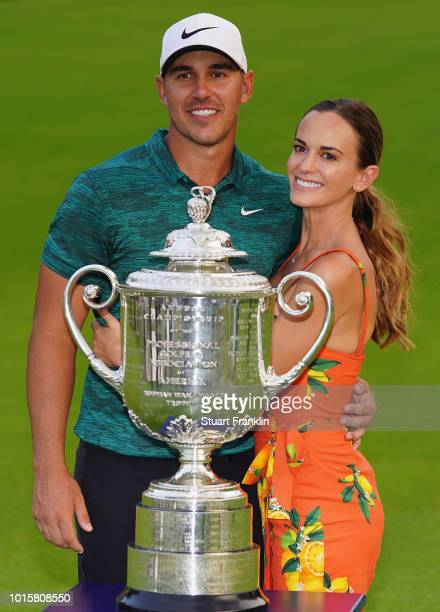 Brooks Koepka of the United States poses with his girlfriend Jena Sims and the Wanamaker Trophy on the 18th green after winning the 2018 PGA...