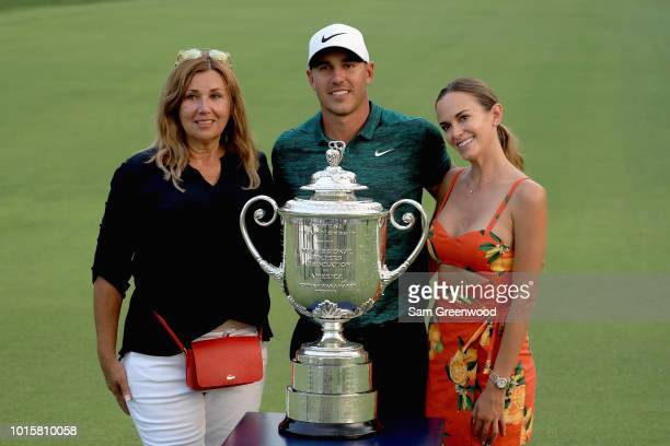 Brooks Koepka of the United States poses with his mother Denise Jakows girlfriend Jena Sims and the Wanamaker Trophy on the 18th green after Koepka...