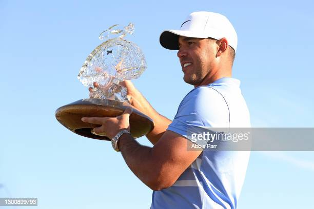 Brooks Koepka of the United States poses with the trophy after winning the Waste Management Phoenix Open at TPC Scottsdale on February 07, 2021 in...