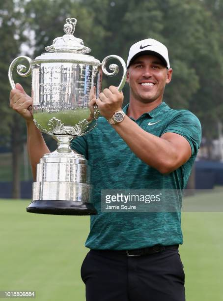 Brooks Koepka of the United States poses with the Wanamaker Trophy on the 18th green after winning the 2018 PGA Championship with a score of -16 at...