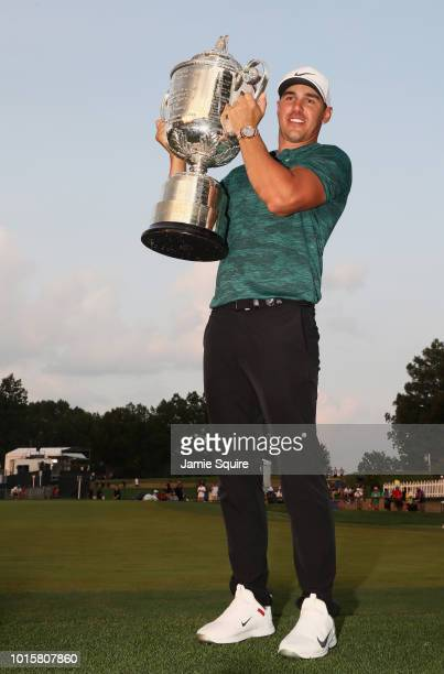 Brooks Koepka of the United States poses with the Wanamaker Trophy on the 18th green after winning the 2018 PGA Championship with a score of 16 at...