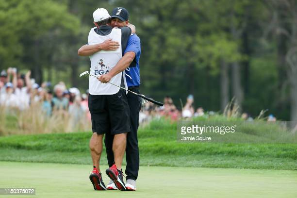 Brooks Koepka of the United States reacts to his putt on the 18th green as he hugs caddie Ricky Elliott during the final round of the 2019 PGA...