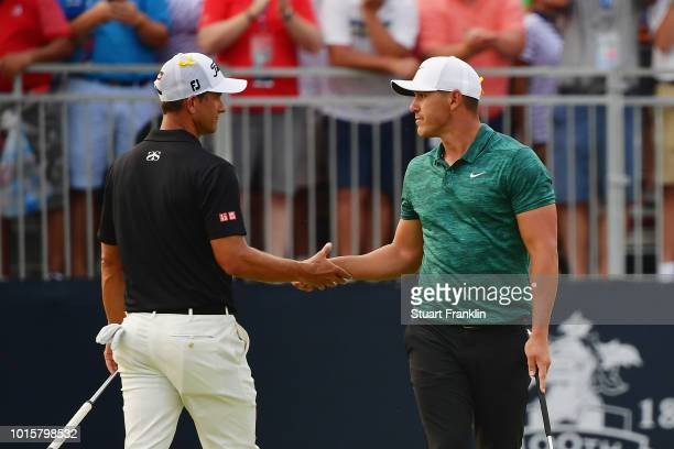 Brooks Koepka of the United States shakes hands with Adam Scott of Australia on the 18th green after winning the 2018 PGA Championship with a score...