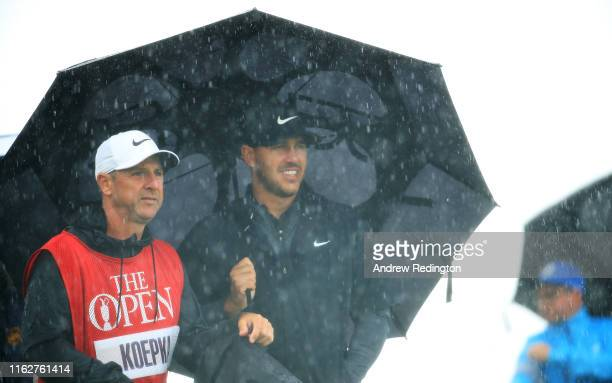 Brooks Koepka of the United States shelters under an umbrella with caddie, Ricky Elliot on the 3rd hole during the first round of the 148th Open...