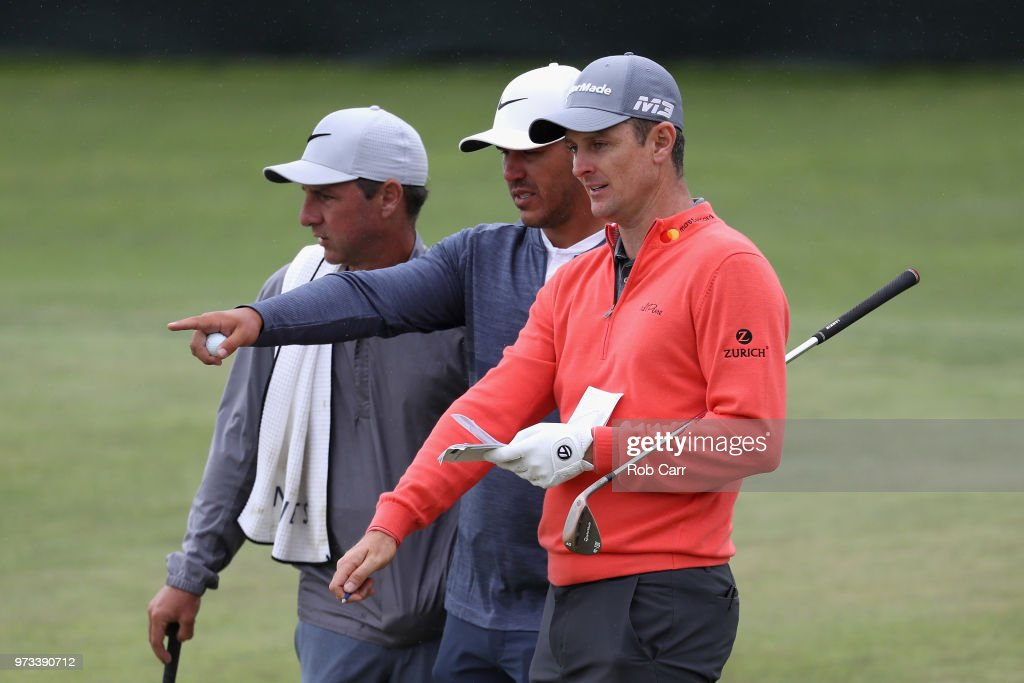 Brooks Koepka of the United States talks with Justin Rose of England during a practice round prior to the 2018 U.S. Open at Shinnecock Hills Golf Club on June 13, 2018 in Southampton, New York.