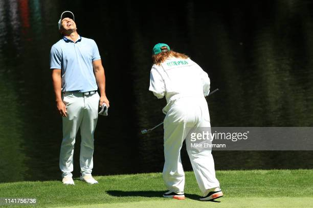 Brooks Koepka of the United States to a putt by his mother Denise Jakows during the Par 3 Contest prior to the Masters at Augusta National Golf Club...