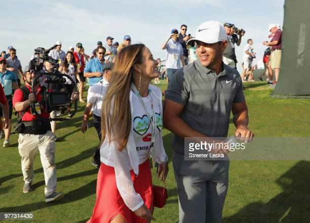 Brooks Koepka of the United States walks off the 18th green with girlfriend Jena Sims during the final round of the 2018 US Open at Shinnecock Hills...