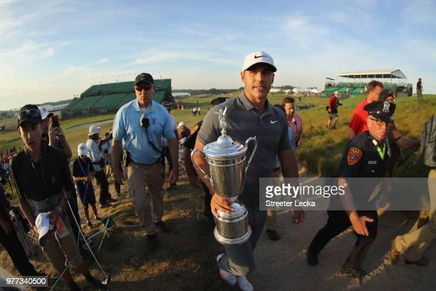 Brooks Koepka of the United States walks off the course with the US Open Championship trophy after winning the 2018 US Open at Shinnecock Hills Golf...