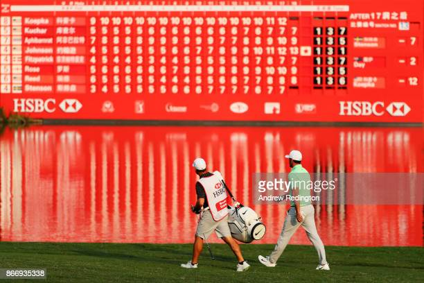 Brooks Koepka of the United States walks with his caddie Ricky Elliott on the 18th hole during the second round of the WGC HSBC Champions at Sheshan...