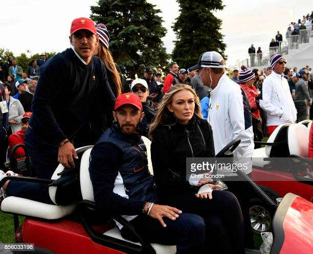 Brooks Koepka of the US Team rides with Dustin Johnson of the US Team and fiance Paulina Gretzky ride in a golf cart during the afternoon fourball...