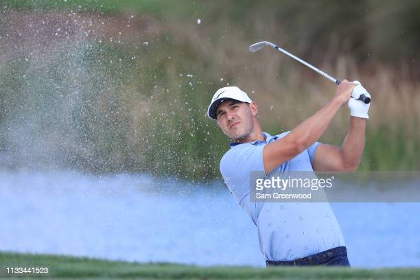 Brooks Koepka plays a shot from a bunker on the third hole during the final round of the Honda Classic at PGA National Resort and Spa on March 03...