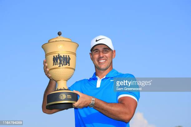 Brooks Koepka poses with the trophy after winning the World Golf Championship-FedEx St Jude Invitational at TPC Southwind on July 28, 2019 in...