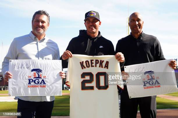 Brooks Koepka, Rich Aurilia, and Randy Winn pose after trading a signed pin flag and jersey during PGA Championship Media Day at Oracle Park on...