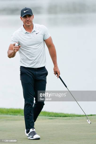 Brooks Koepka waves to fans after making a putt on the eighteenth hole green during the first round of The Honda Classic at PGA National Champion...