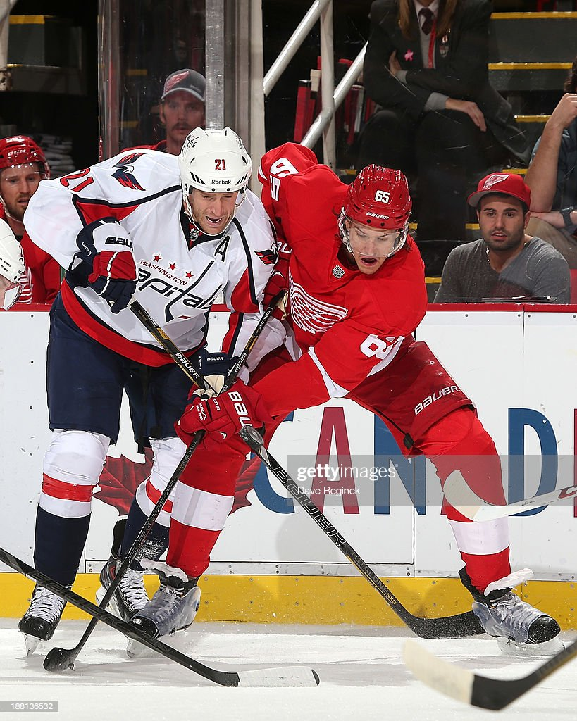 Brooks Laich #21 of the Washington Capitals and Danny DeKeyser #65 of the Detroit Red Wings battle for the puck during an NHL game at Joe Louis Arena on November 15, 2013 in Detroit, Michigan.