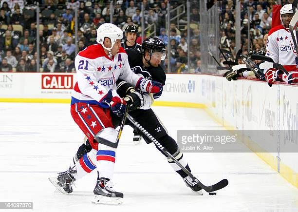 Brooks Laich of the Washington Capitals and Paul Martin of the Pittsburgh Penguins battle for a puck during the game at Consol Energy Center on March...