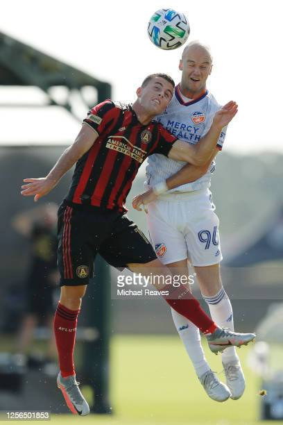 Brooks Lennon of Atlanta United and Andrew Gutman of FC Cincinnati battle for a header during a Group E match as part of the MLS Is Back Tournament...
