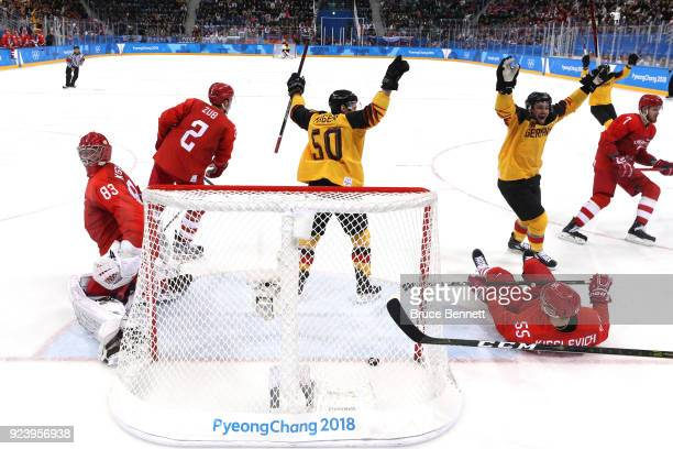 Brooks Macek and Patrick Hager of Germany celebrate after a goal by teammate Felix Schutz in the second period against Vasili Koshechkin of Olympic...