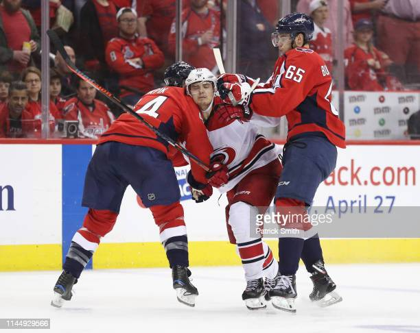 Brooks Orpik and Andre Burakovsky of the Washington Capitals combine to stop Sebastian Aho of the Carolina Hurricanes during the second overtime in...