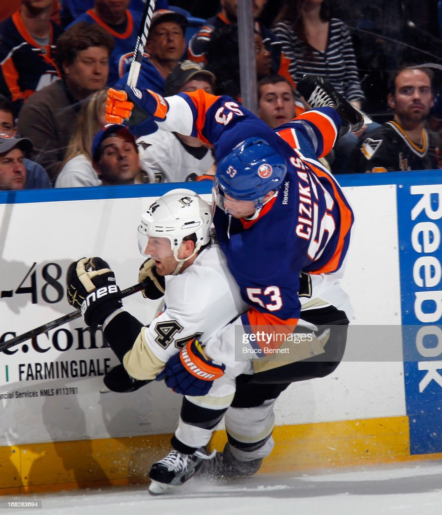 Brooks Orpik #44 of the Pittsburgh Penguins checks Casey Cizikas #53 of the New York Islanders during the second period in Game Four of the Eastern Conference Quarterfinals during the 2013 NHL Stanley Cup Playoffs at the Nassau Veterans Memorial Coliseum on May 7, 2013 in Uniondale, New York.