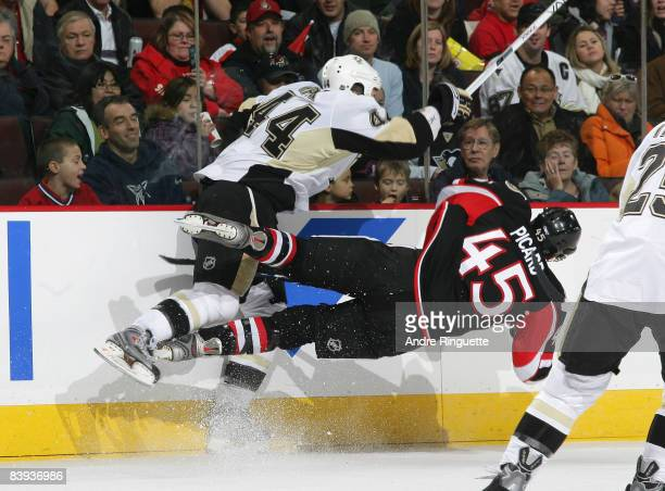 Brooks Orpik of the Pittsburgh Penguins levels Alexandre Picard of the Ottawa Senators at Scotiabank Place on December 6, 2008 in Ottawa, Ontario,...