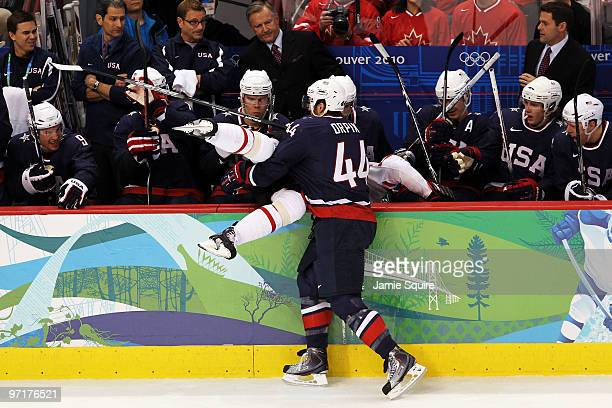 Brooks Orpik of the United States checks a Team Canada member over the boards during the ice hockey men's gold medal game between USA and Canada on...