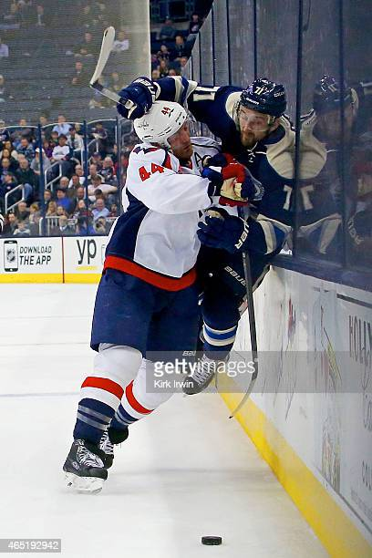Brooks Orpik of the Washington Capitals checks Nick Foligno of the Columbus Blue Jackets into the glass during the second period on March 3 2015 at...
