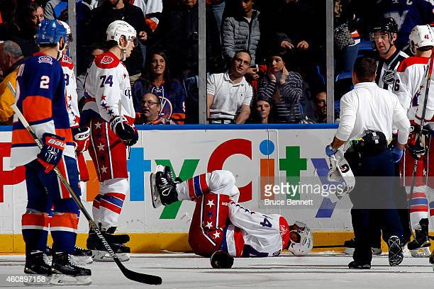 Brooks Orpik of the Washington Capitals lays on the ice after an injury against the New York Islanders during a game at the Nassau Veterans Memorial...