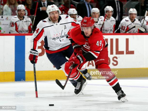 Brooks Orpik of the Washington Capitals trails Victor Rask of the Carolina Hurricanes as he advances the puck through the neutral zone during an NHL...