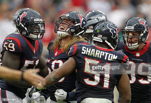 Brooks Reed of the Houston Texans celebrates with Whitney Mercilus Darryl Sharpton and JJ Watt after a a defensive stop at Reliant Stadium on...