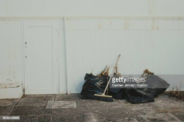 Broom And Black Garbage Bags By White Wall