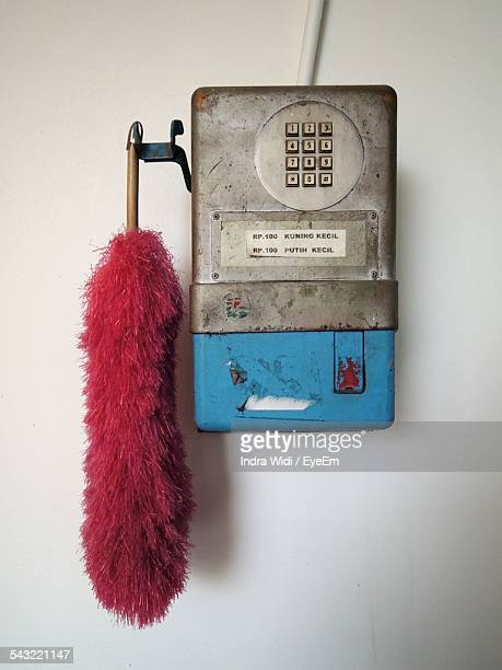 Broom Attached To Abandoned Telephone On Wall