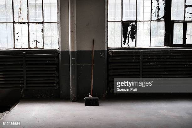 A broom lays against a wall in an old factory building in Industrial City a historic shipping warehousing and manufacturing complex on the waterfront...