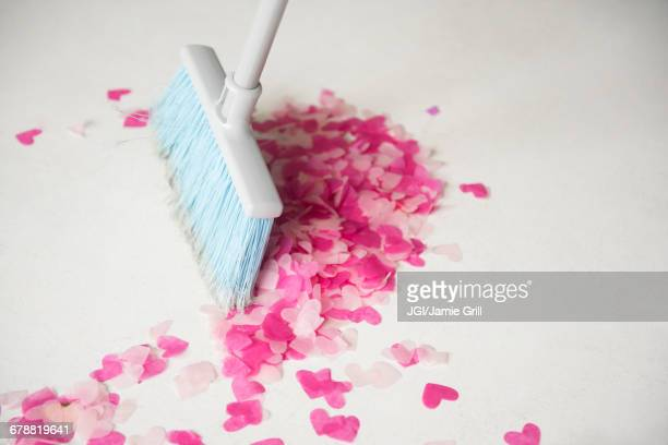 Broom sweeping heart-shape confetti on floor
