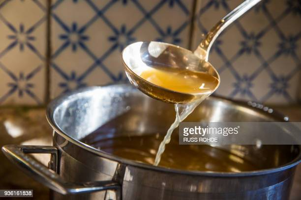 broth being ladled from saucepan - gravy stock photos and pictures