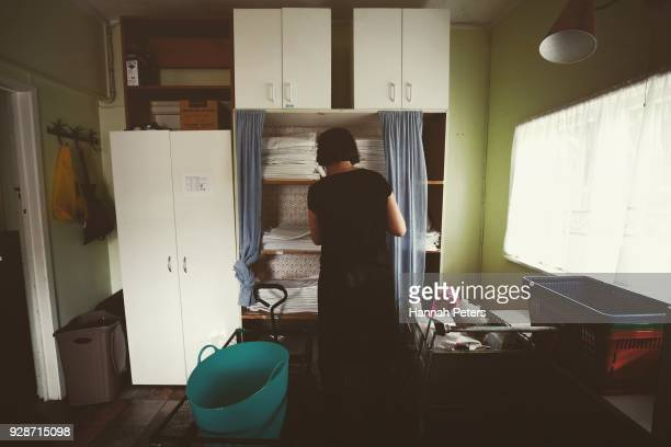Brothel owner and director Antonia Murphy gathers fresh bed linen to change and clean the room in between clients at The Bach an ethical escort...