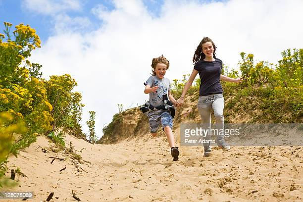 brother, 9 years old and sister, 15 years old, running down sand dunes, s. wales, uk - 14 15 years stock pictures, royalty-free photos & images