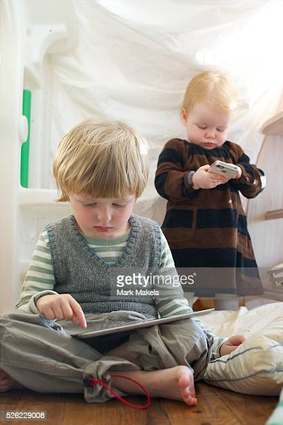 A brother aged 4 and sister aged 1 play with an iPad and iPhone