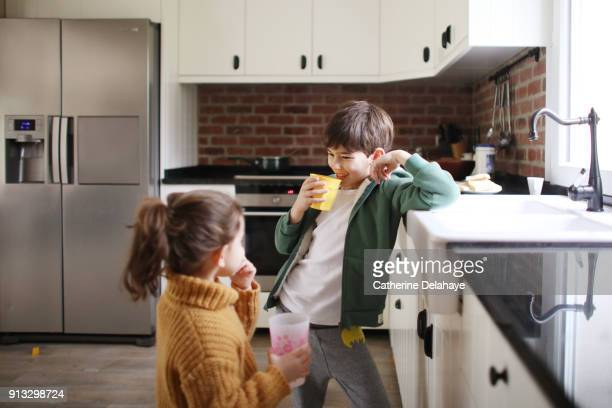 a brother and a sister drinking water in the kitchen - delahaye stock photos and pictures