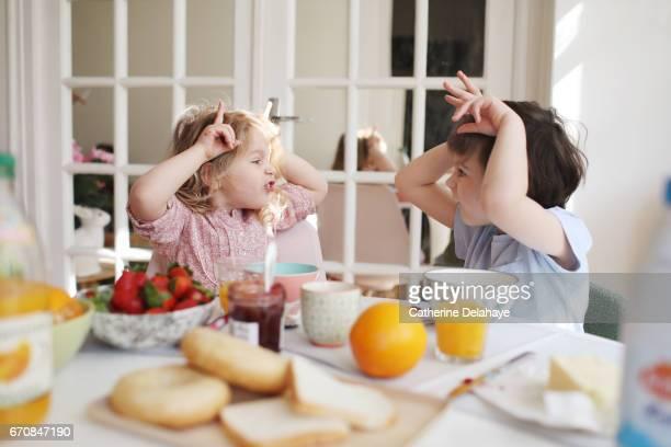 a brother and a sister having their breakfast - frühstück stock-fotos und bilder