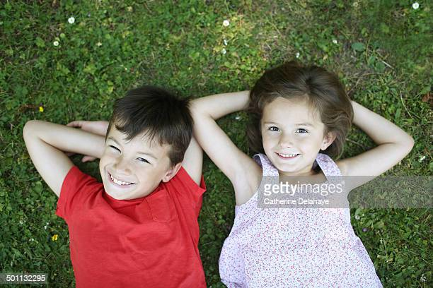 A brother and a sister laying in the grass