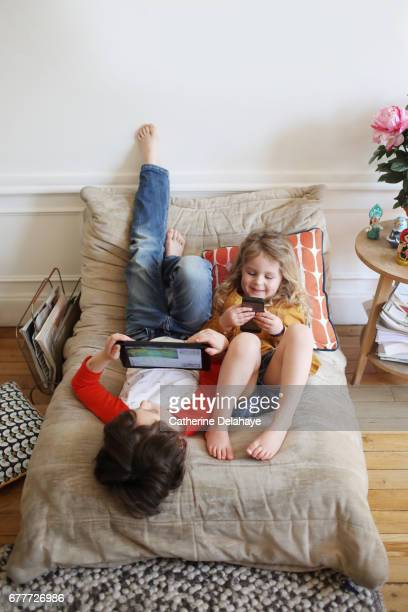 a brother and a sister looking at a tablet and a smartphone - nur kinder stock-fotos und bilder
