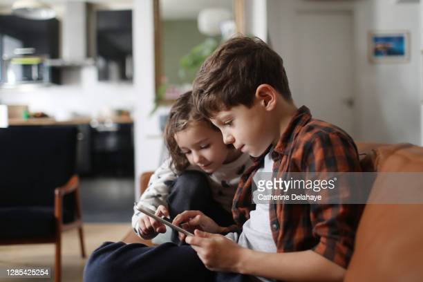 a brother and a sister looking at a tablet at home - sister stock pictures, royalty-free photos & images