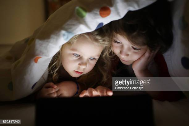 a brother and a sister looking at a tablet - enfant stockfoto's en -beelden