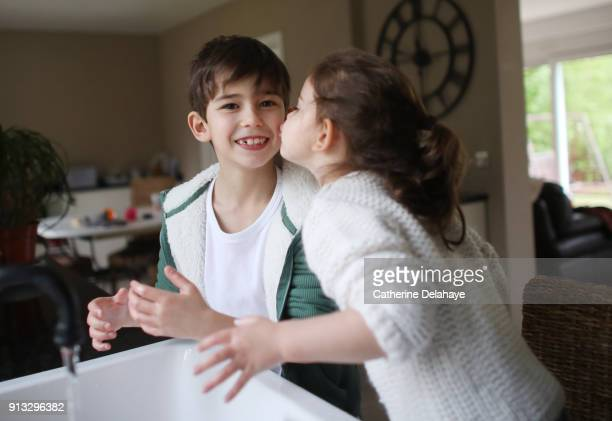 A brother and a sister washing her hands in the kitchen